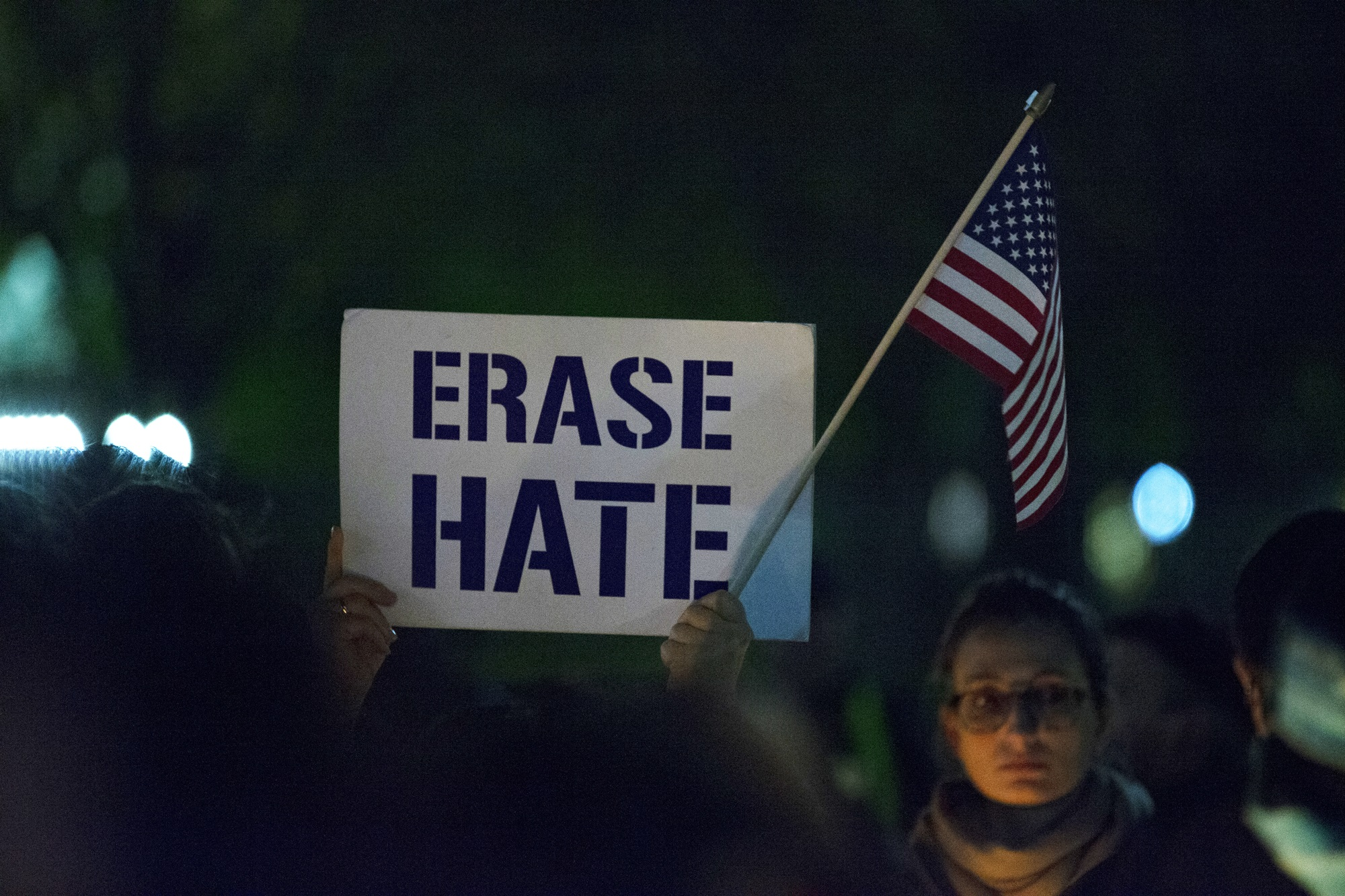 "A person holding up a sign that says ""Erase Hate"" at a rally"
