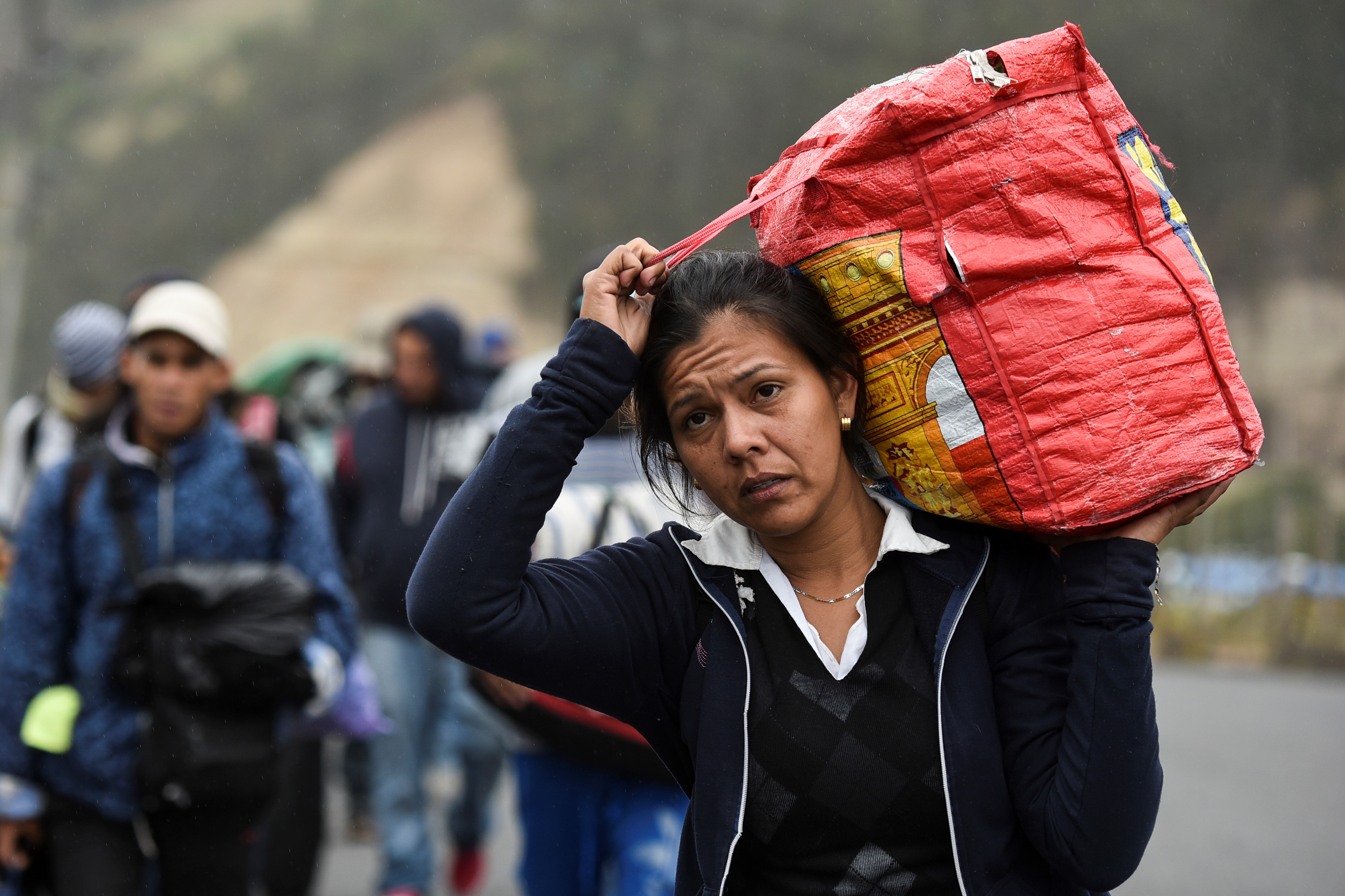 A Venezuelan migrant woman heading to Peru carries a bag as she walks along the Panamerican highway in Tulcan, Ecuador, after crossing from Colombia, on August 21, 2018. - Ecuador announced on August 16 that Venezuelans entering the country would need to show passports from August 18 onwards, a document many are not carrying. And Peru followed suit on August 17, announcing an identical measure due to begin on August 25. (Photo by Luis ROBAYO / AFP)  (Photo credit should read LUIS ROBAYO/AFP/Getty Images)