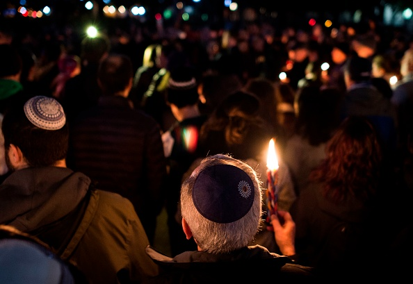 A Jewish person holding a Havdalah candle at a rally